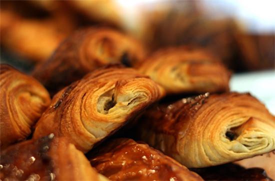巧克力面包满盖新鲜香蕉;充满奶油的蜗牛面包上面